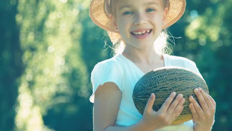 Child-Giving-The-Viewer-A-Melon-Girl-Promoting-Melon-And-And-Smiling-At-Camera