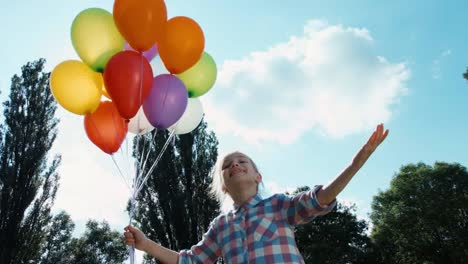 Child-Holding-A-Bunch-Of-Balloons-And-Stretching-At-Sky-Sunlight
