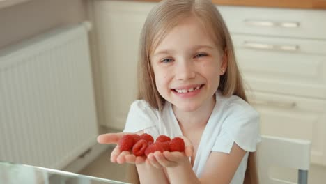 Child-Holding-A-Handful-Of-Raspberries-And-Gives-Its-Audience