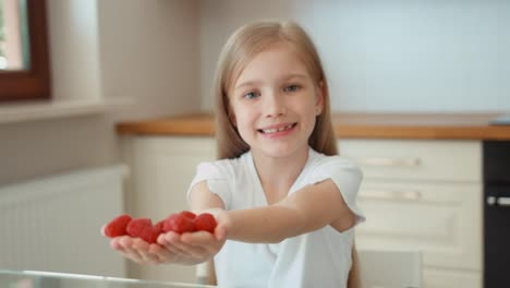 Child-Holds-A-Handful-Of-Raspberries-And-Gives-Its-Audience-Looking-At-Camera
