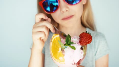 Child-In-Sunglasses-Eating-Ice-Cream-And-Smiling-At-The-Camera-On-The-White