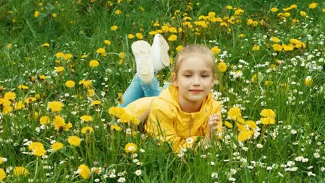 Child-Lying-On-The-Grass-Among-Yellow-Flowers-Zooming