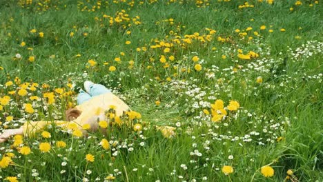 Child-Lying-On-The-Grass-Among-Yellow-Flowers