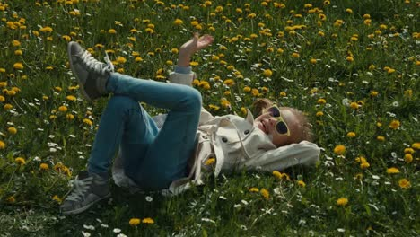 Child-Lying-On-The-Grass-And-Does-Not-Do-Anything-Child-Waving-At-The-Camera