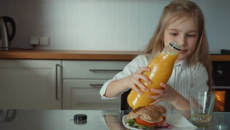 Child-Pouring-Orange-Juice-Into-A-Glass-And-Drinks-It-In-The-Kitchen