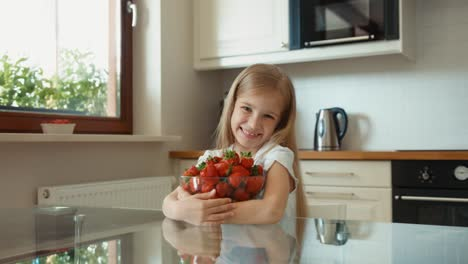 Child-Rubs-His-Hands-Girl-Hugging-A-Large-Plate-Of-Strawberries-And-Looking