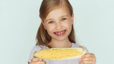 Child-Showing-Corn-Girl-Holding-Corn-In-The-Hands-Closeup