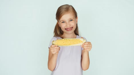 Child-Showing-Corn-Girl-Holding-Corn-In-The-Hands