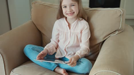 Child-Sitting-On-The-Couch-And-Is-Online-With-Tablet-PC-Girl-Smiling-And-Loo