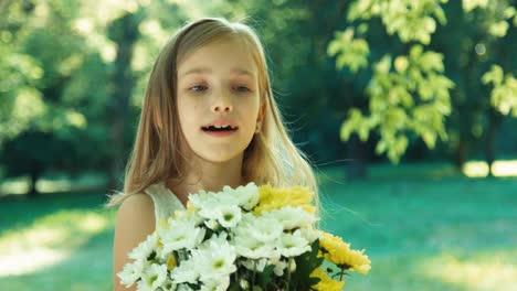 Niño-Olfateando-Flores-Y-Estornudos-Y-Mirando-A-Cámara