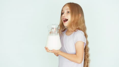 Child-Sniffing-Milk-Child-Showing-Jug-Of-Milk-At-Camera