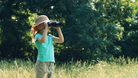 Kind-Steht-Im-Gras-Und-Hält-Ein-Fernglas-Mädchen-Beobachtet-Tiere