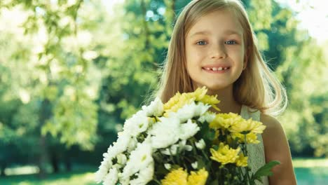 Child-Turns-Around-At-Camera-Portrait-Girl-Hugging-Bouquet-Of-Flowers