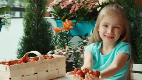 Child-With-Handful-Of-Strawberries-Looking-At-Camera-Proffers-Fruit-To-Viewer