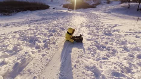 Children-Riding-Down-A-Snow-Hill-On-A-Toboggan