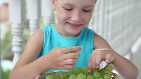 Closeup-Portrait-Of-A-Girl-Which-Eating-Grapes-The-Child-Looking-At-Camera