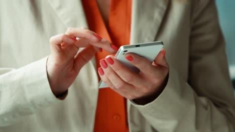 Closeup-Manos-De-Empresaria-Mediante-Teléfono-Móvil-Y-Sonriendo