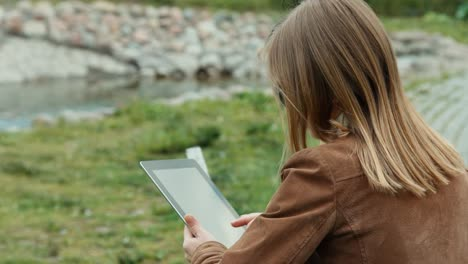 Close-up-portrait-of-young-adult-woman-using-tablet-and-sitting-on-the-bench