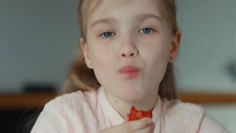 Closeup-Portrait-Child-Eating-A-Big-Red-Strawberry