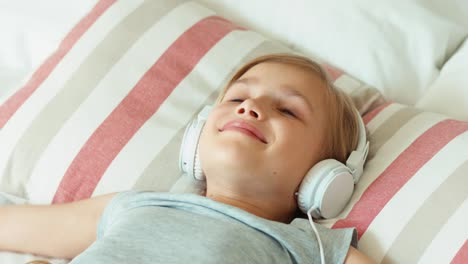 Closeup-Portrait-Girl-Child-Listening-Music-In-Headphones-And-Resting-Lying