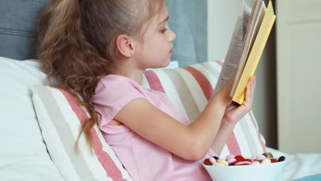 Closeup-Portrait-Girl-Child-Reading-A-Book-And-Eating-A-Sweets