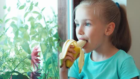Closeup-Portrait-Girl-Eating-Banana-And-Sitting-On-The-Windowsill-And-Looking