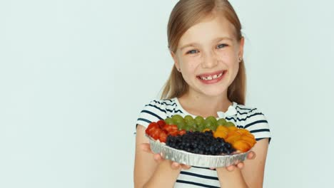 Closeup-Portrait-Girl-Holding-Cake-With-Fruit-Near-Face-On-The-White-Background