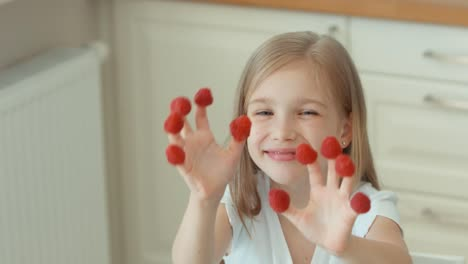Closeup-Portrait-Girl-Indulges-With-Raspberries-And-Laughing-At-The-Camera