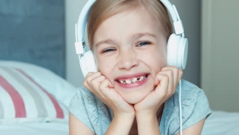 Close-up-of-girl-listening-to-music-on-headphones-and-singing-a-song