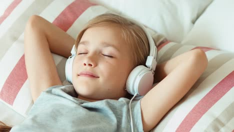 Closeup-Portrait-Girl-Listening-Music-In-Headphones-With-Eyes-Closed-And-Lying