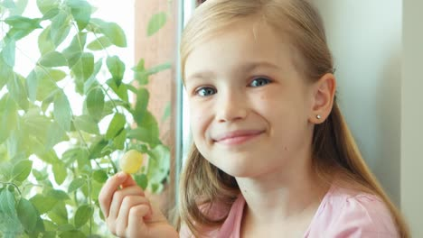 Closeup-Portrait-Girl-Sniffing-And-Eating-Gooseberries-And-Sitting