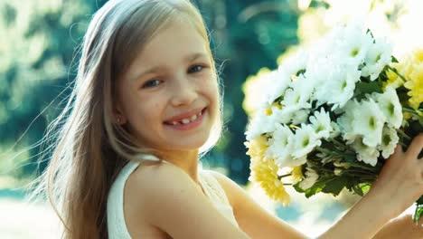 Closeup-Retrato-Niña-Oliendo-Flores-Colegiala-Está-En-Vestido-De-Wite-De-Pie
