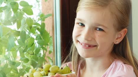 Closeup-Portrait-Girl-Sniffing-Gooseberries-In-The-Bowl-And-Offers-Berries