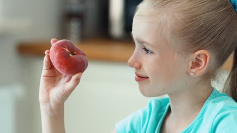 Closeup-Portrait-Girl-Sniffing-Peach-Child-Sitting-At-The-Kitchen-Table