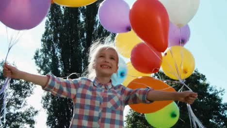 Closeup-Portrait-Girl-Spinning-With-Balloons-And-Looking-At-Camera-Against-Sun
