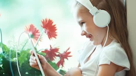 Closeup-Retrato-Chica-Usando-Tablet-Pc-Contra-La-Niña-De-Las-Flores-Escuchando-Música