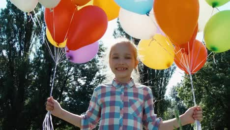 Closeup-Portrait-Girl-Walking-At-Camera-With-Balloons-In-The-Park-And-Spinning