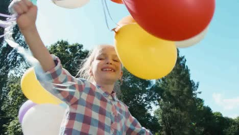 Portrait-Girl-Walking-At-Camera-With-Balloons-In-The-Park-Sunlight