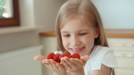 Closeup-Portrait-Girl-Child-Holding-A-Handful-Of-Raspberries-And-Looking