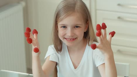 Closeup-Portrait-Girl-Child-Indulges-With-Raspberries-And-Laughing