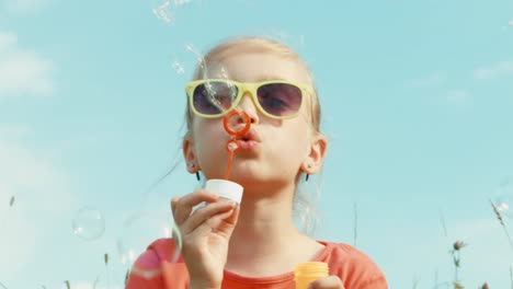 Closeup-Portrait-Happy-Girl-Blowing-Bubbles-Against-The-Sky-And-Smiling