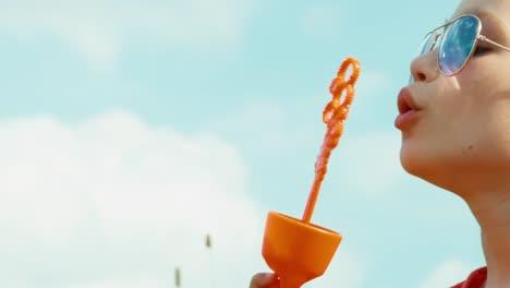 Closeup-Portrait-Happy-Girl-Blowing-Bubbles-Against-The-Sky