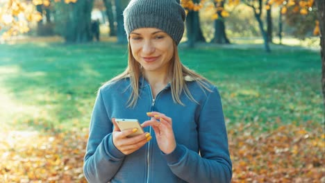 Closeup-Portrait-Happy-Young-Blonde-Woman-Using-Smartphone-Smiling-At-Camera