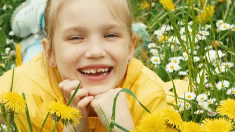 Closeup-Portrait-Laughing-Girl-Lying-In-The-Grass-And-Looking-At-Camera-Zooming