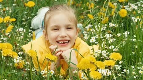 Closeup-Portrait-Laughing-Girl-Lying-In-The-Grass-And-Looking-At-Camera