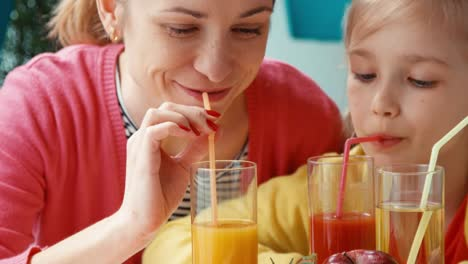 Closeup-Portrait-Mother-And-Daughter-Drinking-Tomato-And-Orange-Juice
