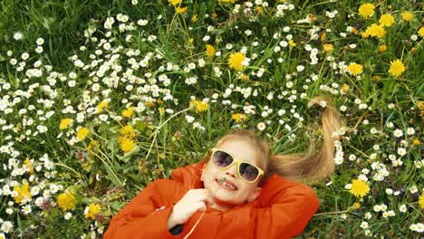 Closeup-Portrait-Of-A-Child-Blowing-Dandelion-The-Child-Lying-On-The-Grass