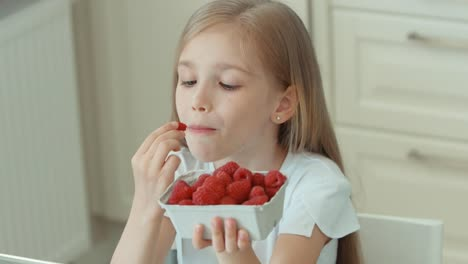 Closeup-Portrait-Of-A-Girl-Eating-Raspberries-And-Laughing-At-Camera