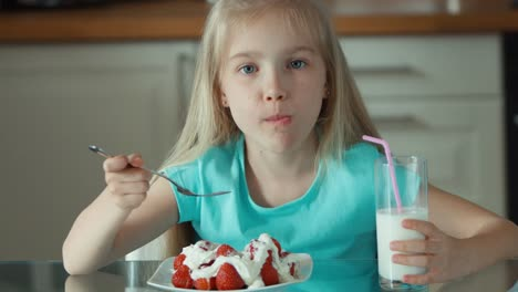 Closeup-Portrait-Of-A-Girl-Eating-Strawberries-With-Cream-And-Drinking-Milk