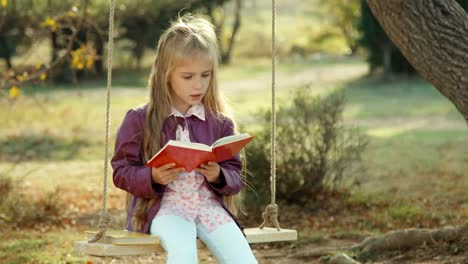 Closeup-Portrait-Of-A-Girl-Reading-A-Book-And-Looking-At-Camera